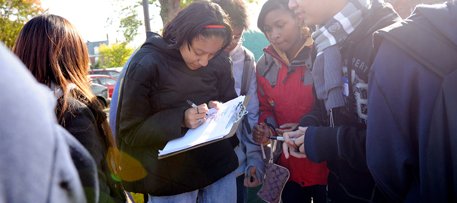Young people filling out something on a clipboard